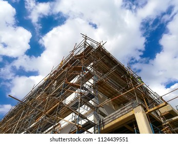 Construction building with scaffolding covered around the building with cloud and blue sky.