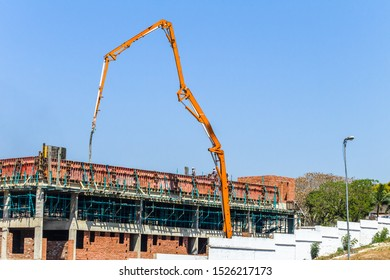 Construction building wet concrete cement pouring of floor via crane  extender arm with pipe mono pumping mechanical hydraulic pistons equipment outdoors blue sky day.
