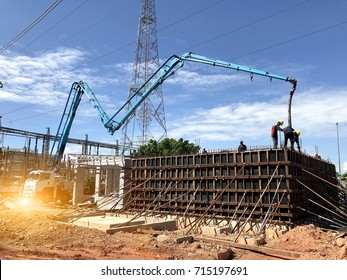 construction building works with automobile concrete pump,selective focus.Two workers are pouring concrete into the walls of a bucket of water.