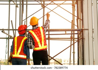 Construction Business : teamwork concept : Young engineer standing behind looking at a building site, wearing a safety helmet.