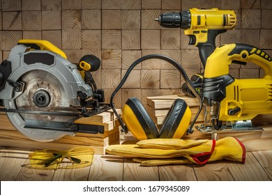 construction carpentry tools electric corded circular saw jigsaw cordless drill earphones gloves goggles on wooden background
