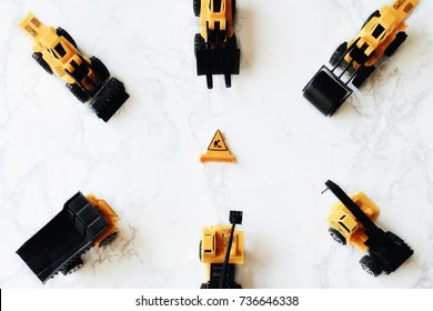 Construction composition. Yellow toys truck, tractor, crane, forklift, backhoe and compaction on white background. Construction cars for building concept. Flat lay, top view.