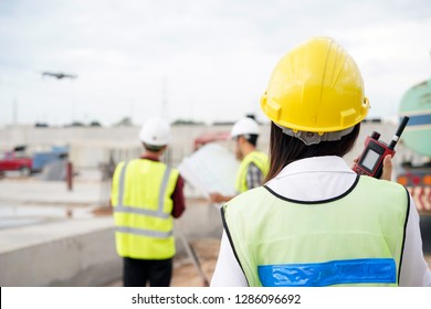 Construction concept of Engineer and Architect working at construction Site with Drone over construction site.