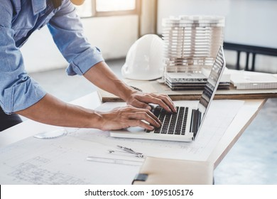 Construction concept, Hands of architect or engineer working for new project plan on blueprint, model building and engineering tools in working site.