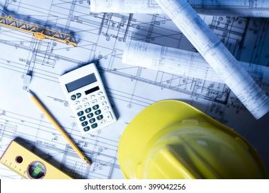 Construction concept. Construction theme, level, ruler, calculator, blueprints rolls, hard hat and pencil