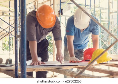 Construction concepts, Engineer and Architect working at Construction Site with blueprint, Vintage effect