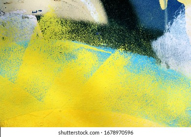 A construction container painted with bright spray paint to remove vandal marks. Blue, yellow, black, white colors on rough grunge surface, good for background with urban accents.