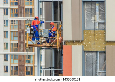 Construction cradle on wall of monolithic house under construction. Electric suspended platform is reliable for working safely at elevated height in accordance with applicable standards Moscow 2019