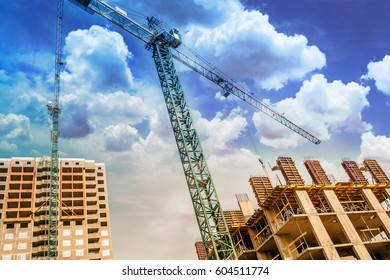 Construction crane above buildings under the clouds
