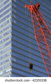 A construction crane with abstract office building facade in the background