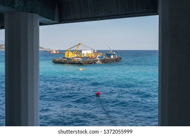 A construction crane barge begins land reclamation work off the coast of Monaco