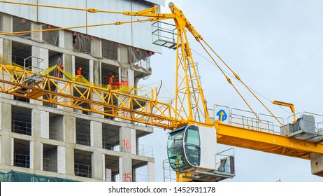 Construction crane cabin closeup on construction site of residential building. A group of workers fixing the protective mesh on the facade on the background.July 2019,Moscow,Russia