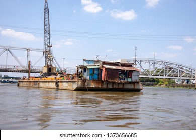 Construction crane on barge by bridge on Saigon River, Vietnam.