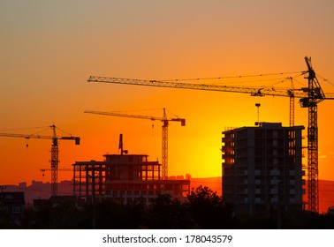 Construction crane and skyscraper at sunset