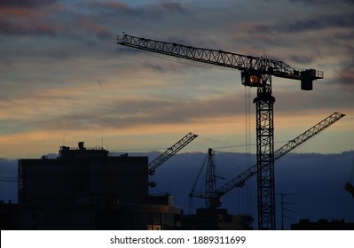 Construction cranes against the background of the evening sky. City. Construction of houses. Tower crane. Lifting crane. Civil engineering