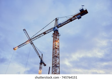 Construction cranes against the dark sky background