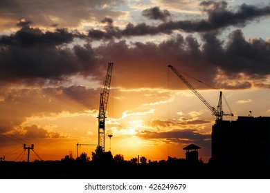 Construction cranes and building silhouettes over sun at sunrise.