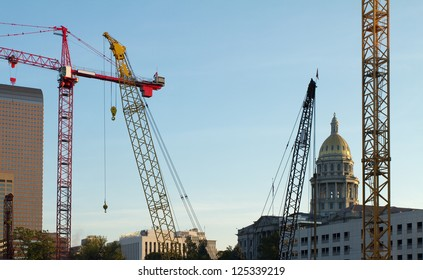 Construction cranes fill the Denver, Colorado skyline, with State Capitol Building.
