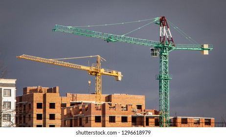 Construction cranes and high-rise building under construction against blue sky.