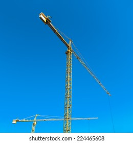 Construction cranes on sky background