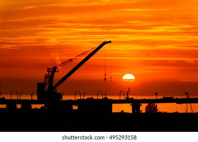 Construction cranes on the Sunset over the sea in Russia