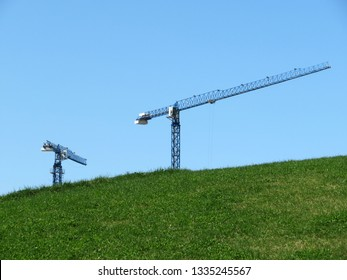 Construction cranes over the green hill on blue sky background. Environmentally friendly construction site, landscape with green grass, building in ecologically clean area, Earth Day concept