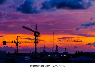 construction cranes silhouettes over amazing sunset sky abstract background in the evening