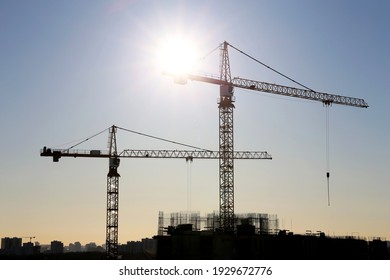 Construction cranes and unfinished residential building on blue sky and sunshine background. Housing construction, apartment block in city