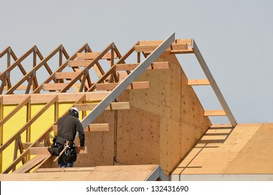 Construction crew working on the roof sheeting and fascia of a new, two story, commercial apartment building in Oregon