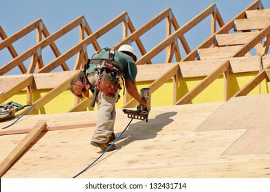 Construction crew working on the roof sheeting of a new, two story, commercial apartment building in Oregon