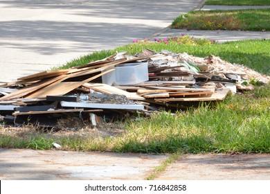 Construction debris piled in curb after flood damage