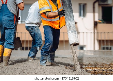 Construction details - worker laying and pouring cement or concrete with automatic pump