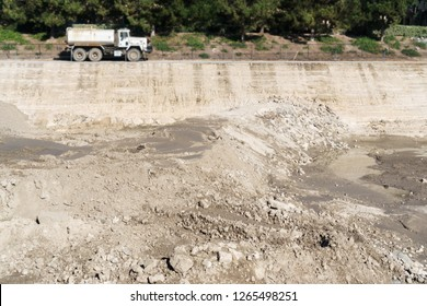 Construction dirt. Rocks and wet soil at excavation site. Blurred truck in background.
