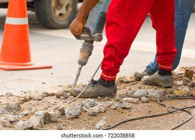 construction drilling repair worker on road surface with heavy duty machine drill motion