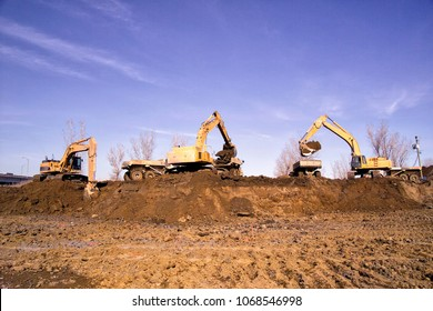 Construction earthworks excavator grader machine loading earth into large truck vehicles