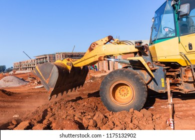 Construction earthworks grader excavator machine bucket tipping earth closeup layout building site.