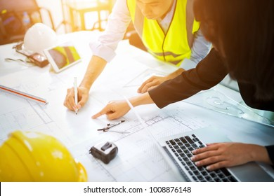 construction engineer architectural design and project blueprints drawings at construction site