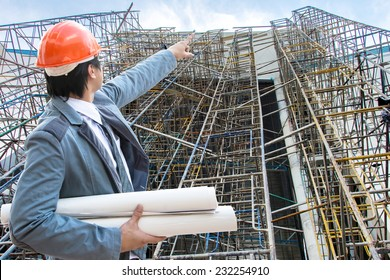Construction engineer with background scaffolding on a construction site.