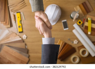 Construction engineer and businessman shaking hands top view close up, desktop with work tools and wood swatches on background