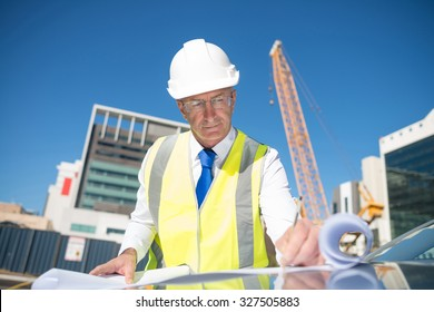 Construction engineer in hardhat making notes in blueprint