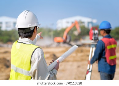 Construction engineer hodling construction drawing with foreman worker checking construction site for new Infrastructure project. photo concept for engineering work.
