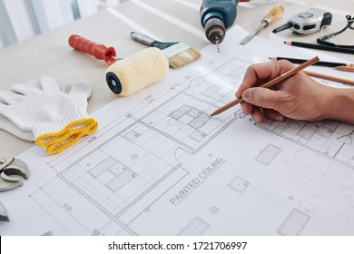 Construction engineer making final corrections in building blueprint or checking size of every detail