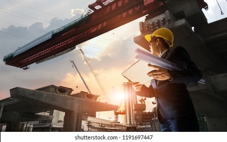 Construction engineer manager supervising progress of BTS Station Construction Project and tablet with blueprint in hands. Cranes in sunset background. Industrial technology 4.0