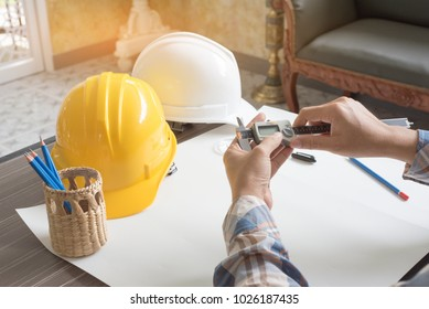 Construction engineer measuring with vernier caliper. Business and Technology concept. Safety helmet and Drawing paper elements. Civil and Drawing sketch theme.