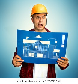 Construction engineer reviewing blueprint and making funny face