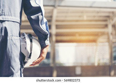 Construction engineer in Safety Suit Trust Team Holding White Yellow Safety hard hat Security Equipment on Construction Site. Hardhat Protect Head for Civil Construction Engineer. Engineering Concept
