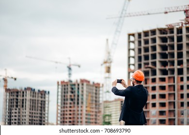 Construction engineer with the smartphone. Pictures of the construction site