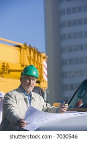 A construction engineer standing leaning on the hood of his truck, and studying plans