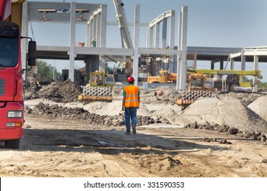 Construction engineer supervising work at building site