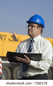 A construction engineer taking notes with a large vehicle behind him